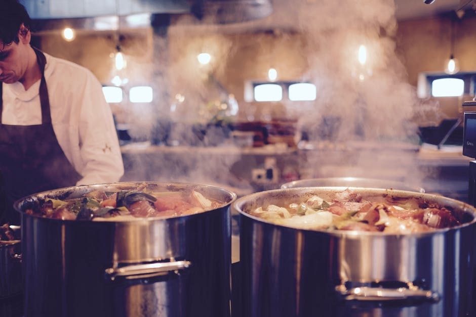 Chef with large cooking pots in restaurant kitchen | SLM Facilities