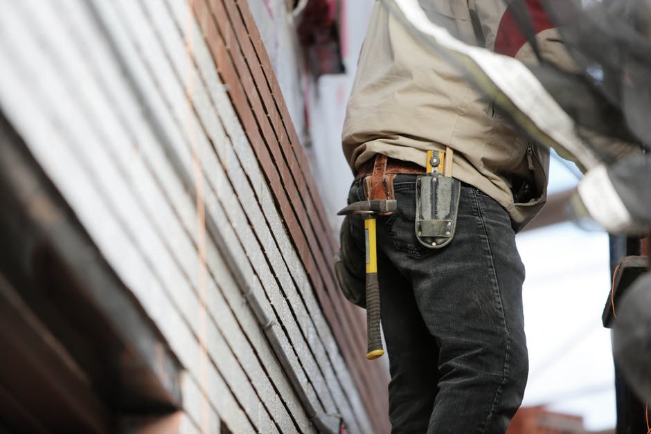 Construction worker with hammer on toolbelt | SLM Facilities