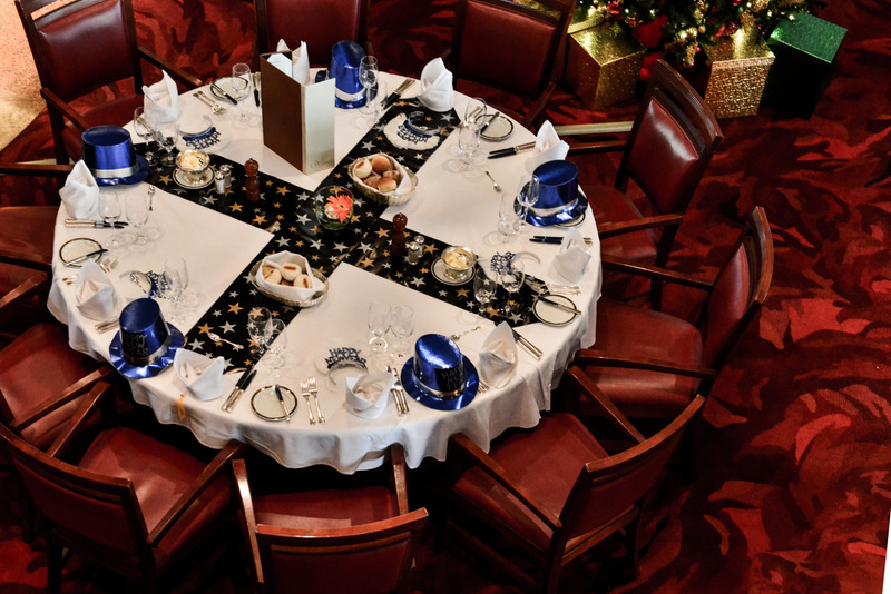 Round dining table set for holiday event with party hats | SLM Facilities