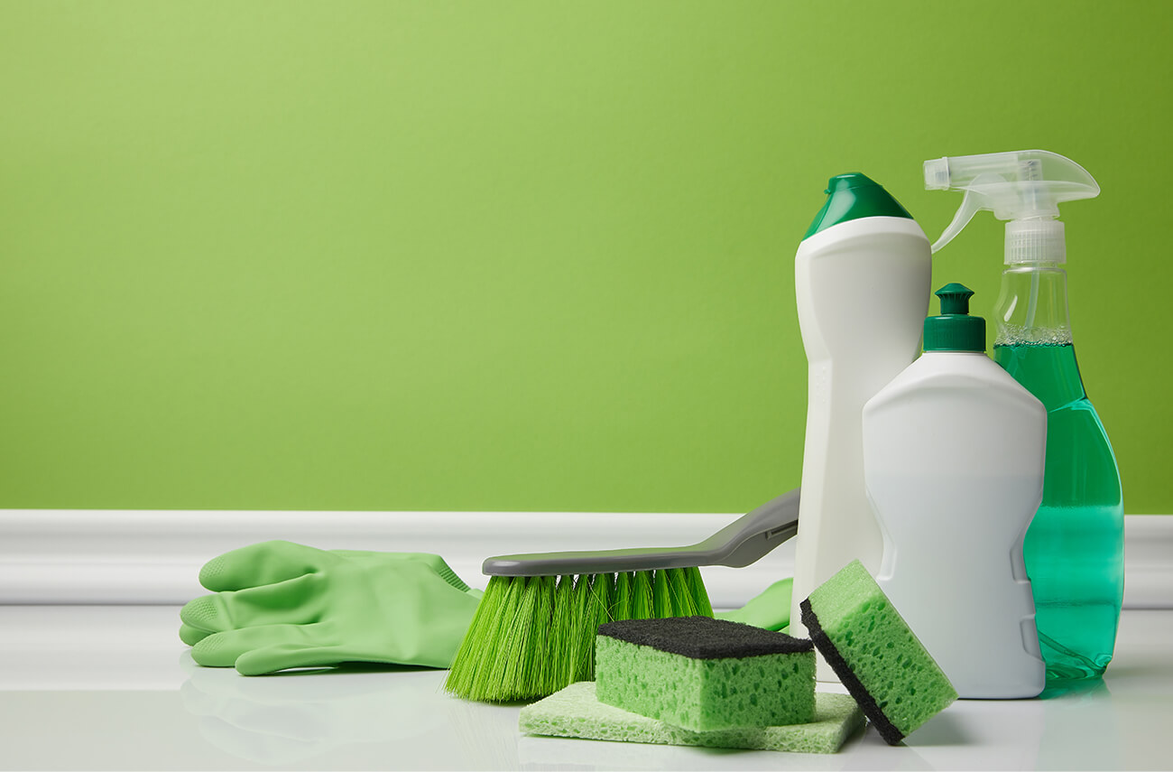 Cleaning supplies against green painted wall | How to Build A Facility Green Cleaning Program | Eco Friendly Cleaning Products | Facility management | SLM Facilities Nationwide